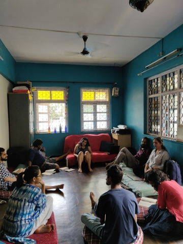 Nidhi interacts with the Blue Ribbon Movement team. Every one is sitting in a circle, listening intently. The room has blue walls and two windows.
