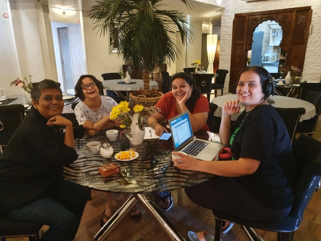 left to right- ratnaboli ray, jeeja ghosh, ishani cordero and nidhi goyal sit around a table, smiling at the camera