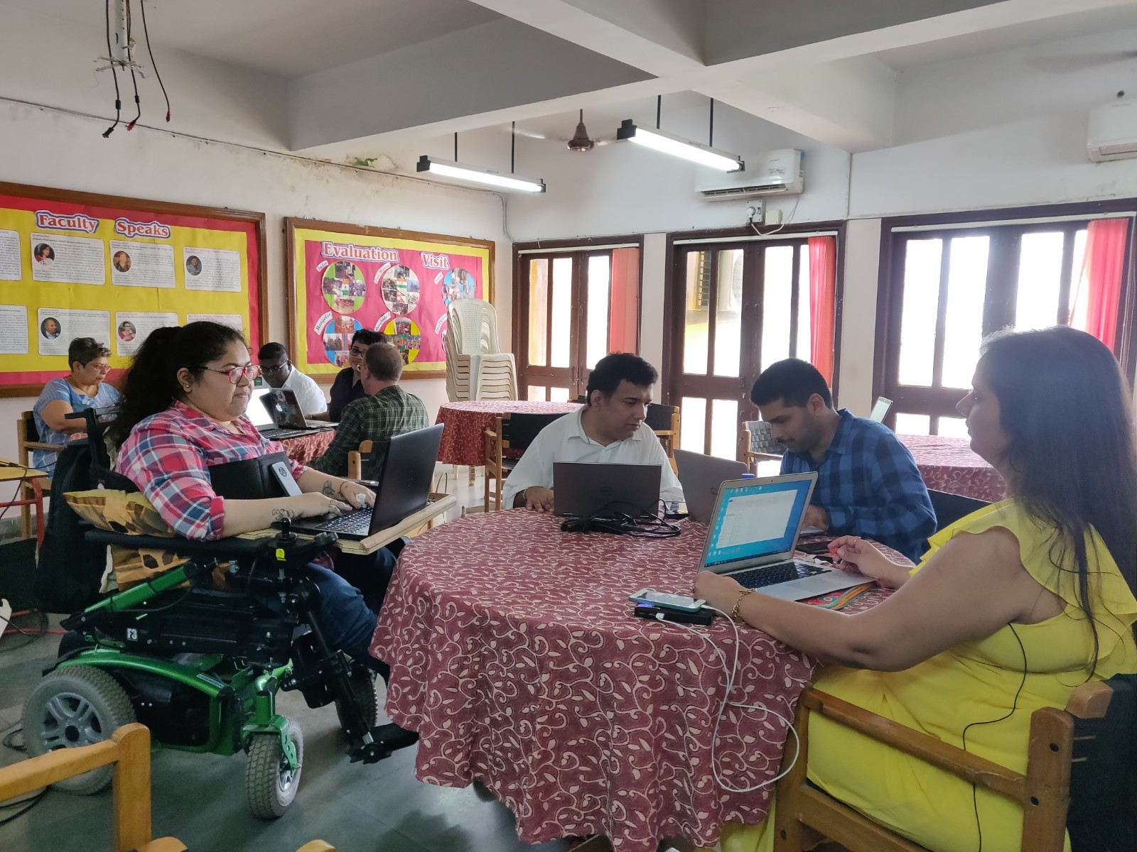 Editathon, august- disabled and non disabled participants sitting around tables and working on laptops at ADAPT, Bandra.. bulletin boards on the wall behind and three windows next to it