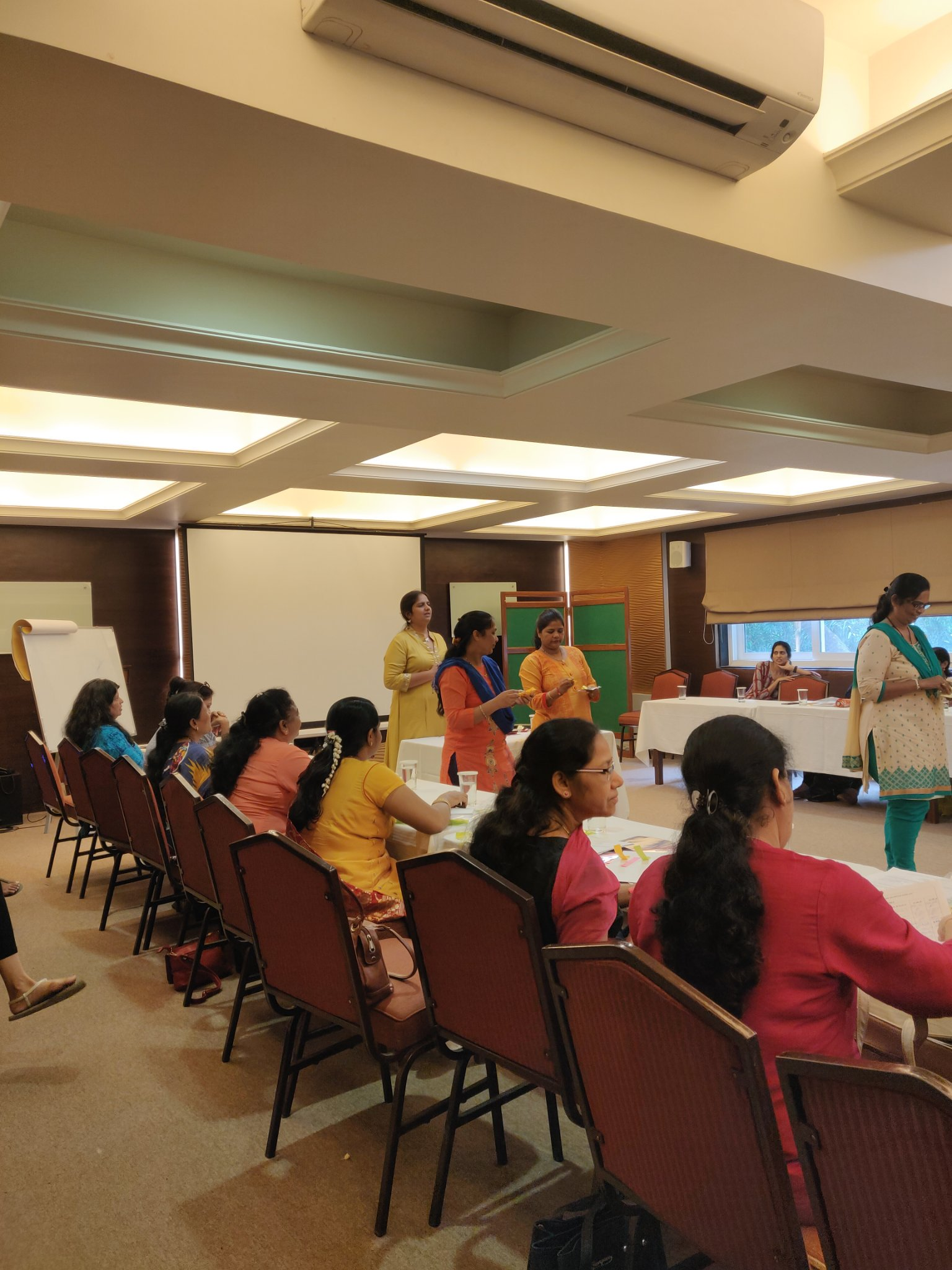 training for BMC workers at YMCA, organised by CEHAT- participants sitting in the room around a U-shaped table. Nidhi goyal standing in the center conducting an activity with three participants