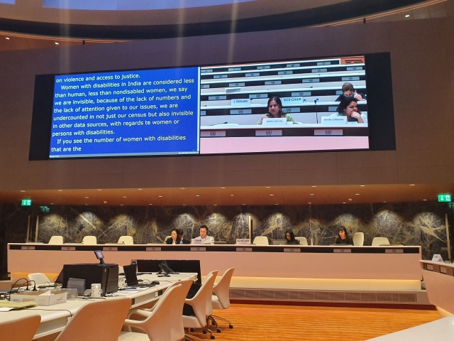 picture of a large screenshowing Nidhi Goyal addressing the UNCRPD committee.  under the screen a table  where four people sit and listen