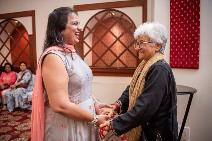 nidhi goyal greeting kamla bhasin. both smiling and holding hands
