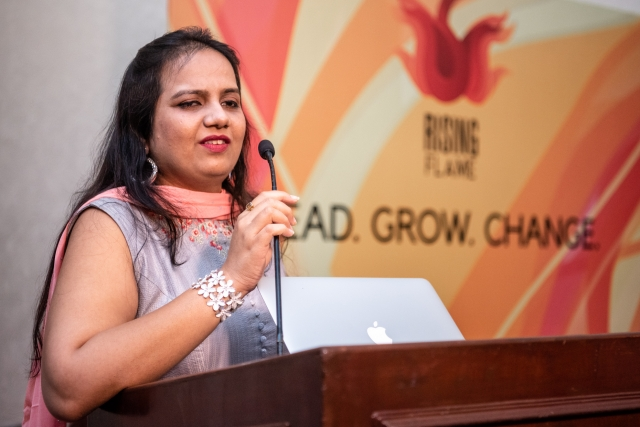 nidhi goyal speaking on the mic at the lead grow change event in delhi. behind her the logo of rising flame under which it reads lead grow change