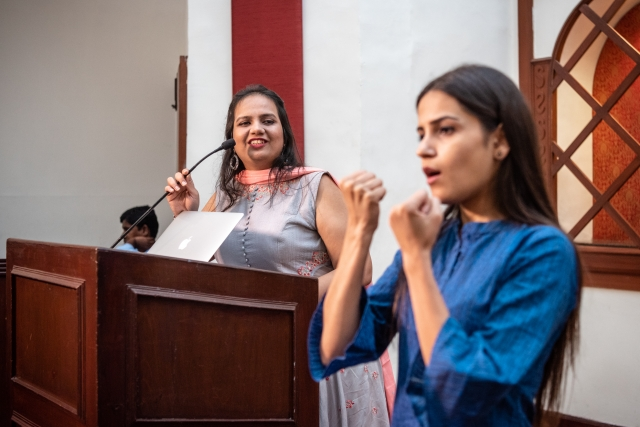 nidhi goyal speaking on the podium; sign language interpreter on her left, signing. at the lead grow change event in delhi