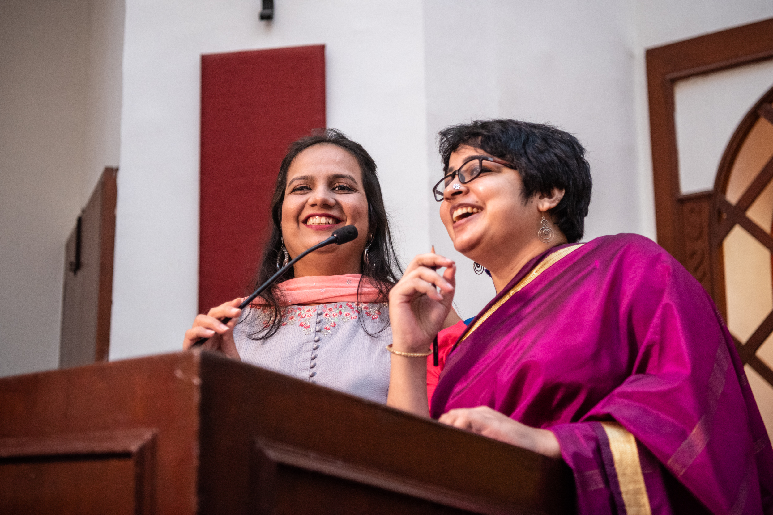 nidhi goyal and srinidhi raghavan speaking on the mic at the podium at lead grow change in delhi.