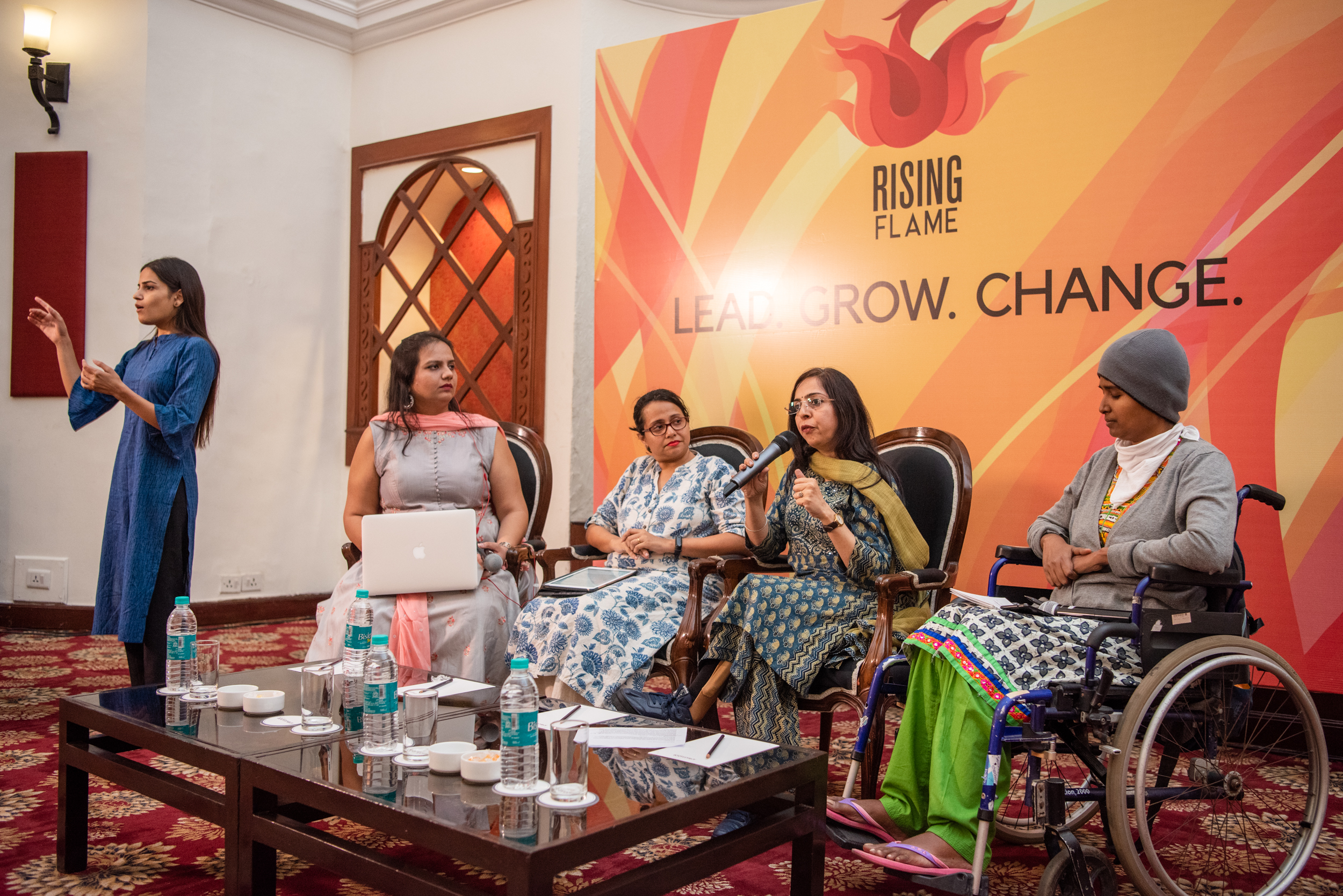Panel left to right- sign language interpreter, Nidhi Goyal, Amba Salelkar, Meenu Bhambani and Smitha Sadasivan. Meenu is speaking, everyone else is looking at her and listening