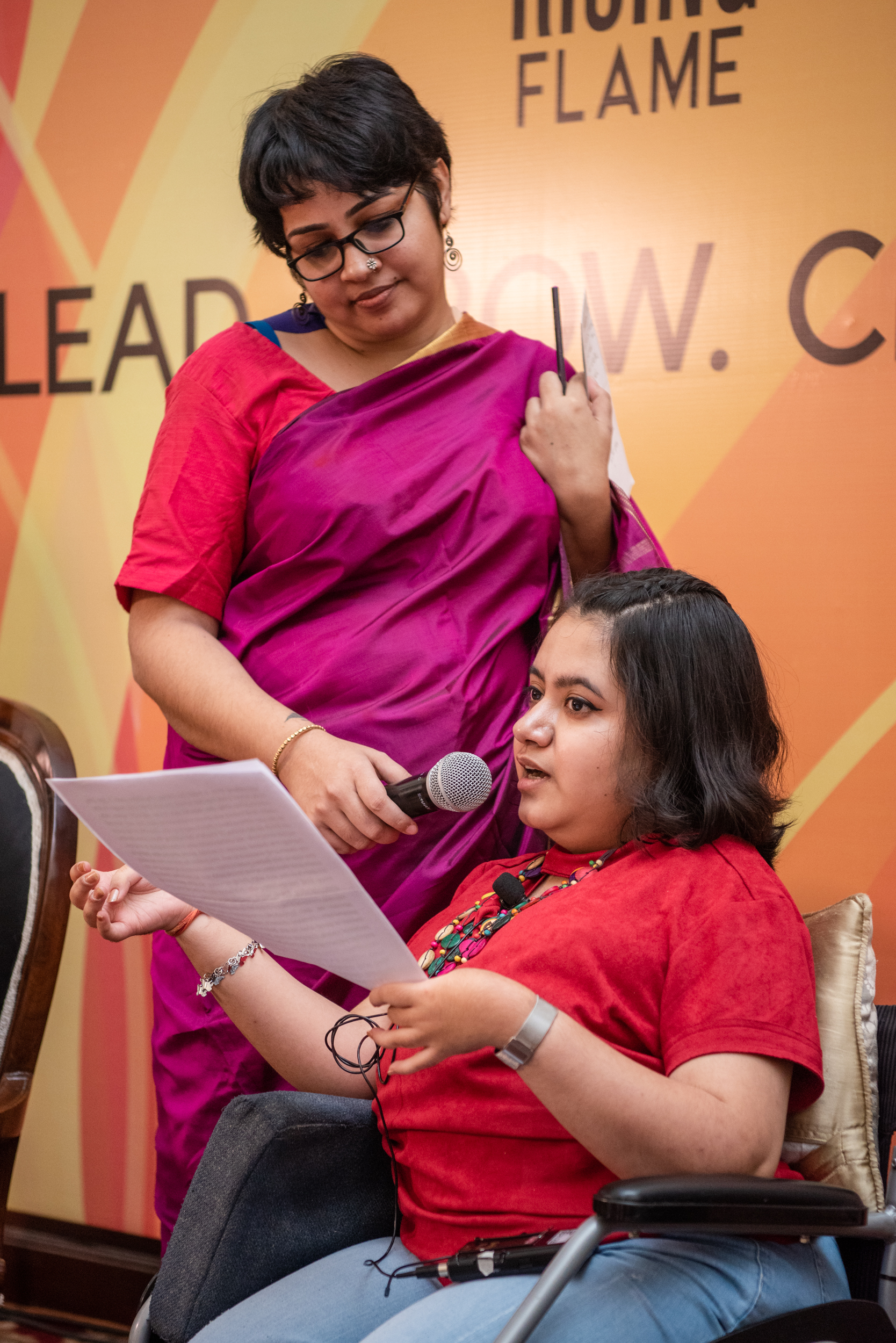 i can lead 2019 fellow kavya mukhija reading from a paper and speaking while srinidhi raghavan holds the mic for her