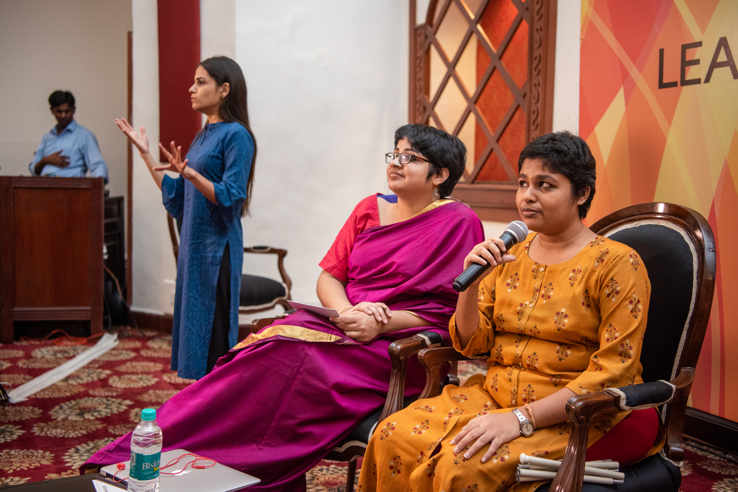 i can lead 2019 fellow Shreelekka sriram speaking in a mic, Srinidhi raghavan sitting beside her and smiling. Sign language interpreter in the background