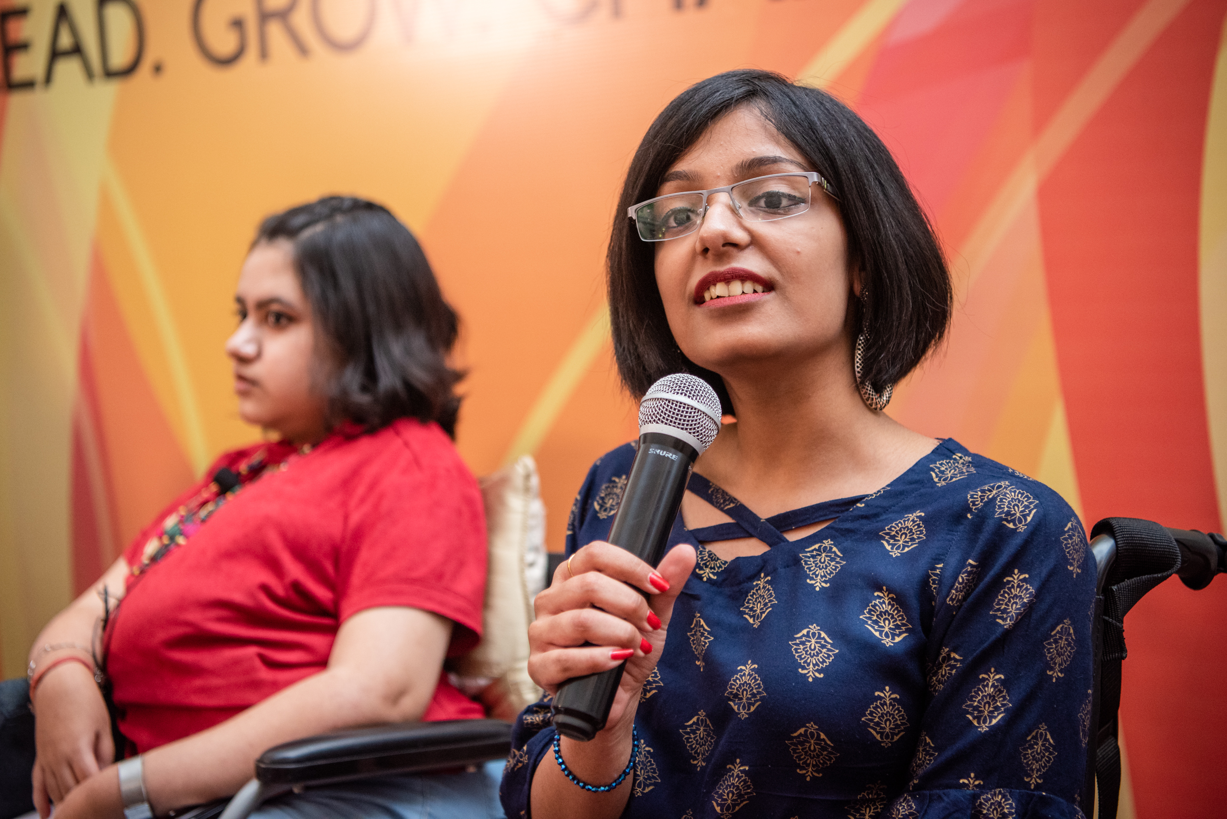 i can lead 2019 fellow pratishtha deveshwar speaking in a mic at lead grow change delhi; kavya in the background