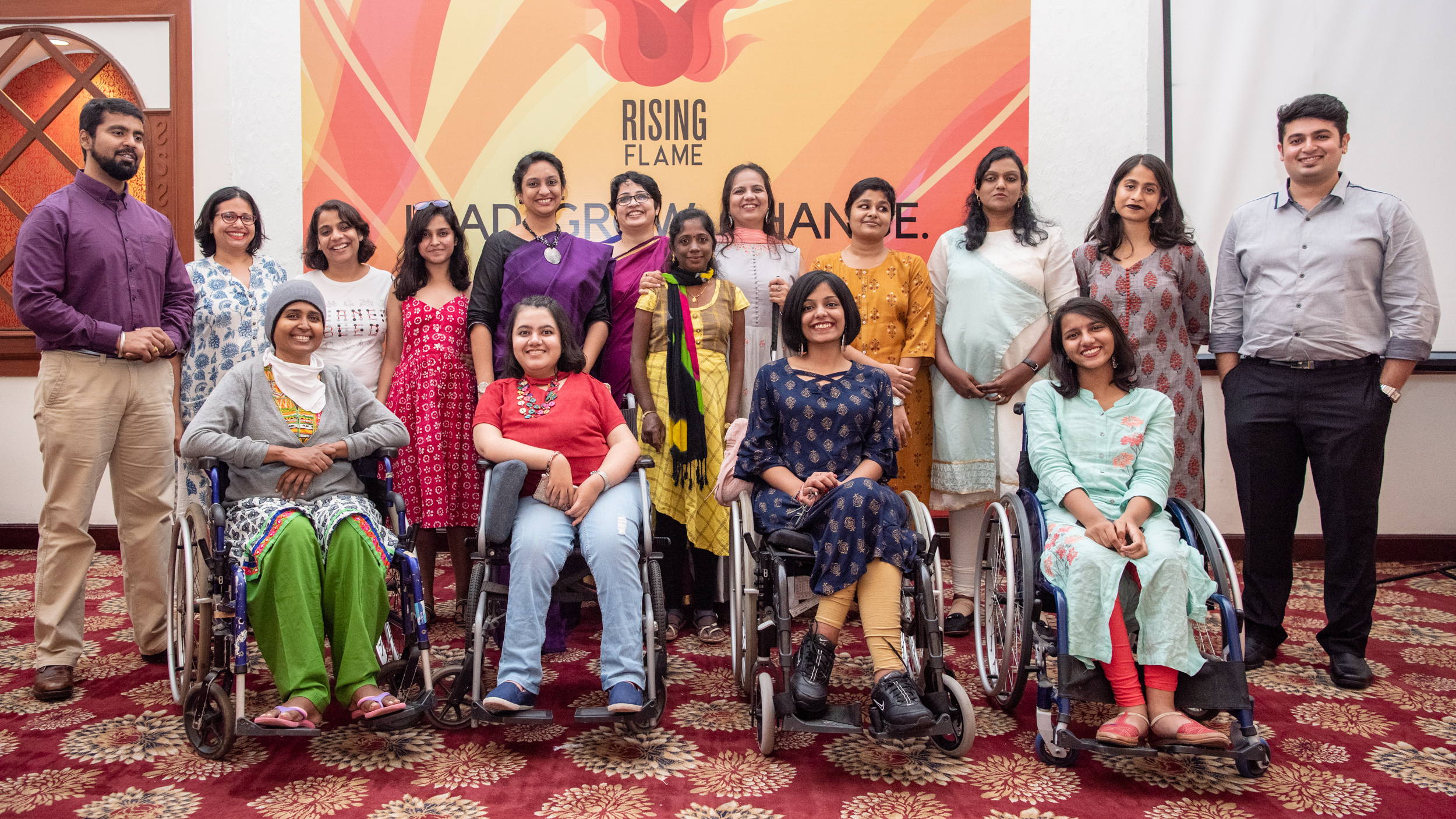 group photograph of rising flame team, I can lead fellows and mentors and some guests at the lead grow change event in delhi. rising flame logo on the wall behind them