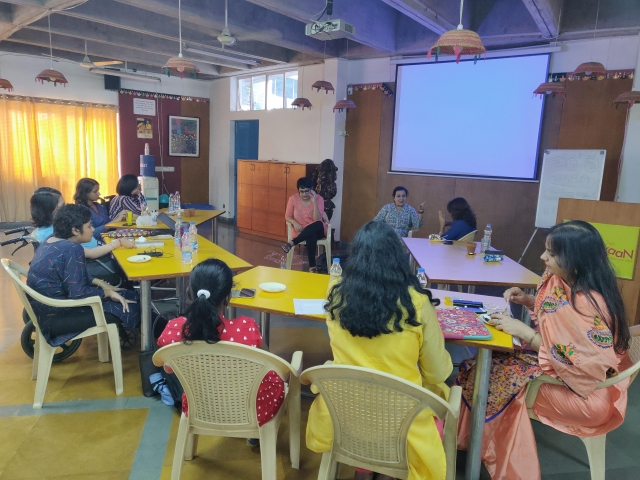 i can lead 2019 fellows sitting around yellow tables; training facilitators srinidhi raghavan, harpriti reddy and sign language interpret preeti saini in the center. a projector screen behind them