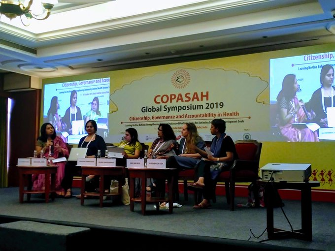 Nidhi Goyal along with Nilangi Naren, Sana Contractor, Sara Van Belle and Rupsa Mallik sitting on a panel at COPASAH 2019.  behind them the panel is being projected on the wall with the words copasah global symposium 2019 in the center