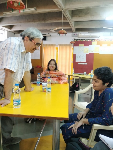 trainer sanjeev kumar interacts with i can lead fellow shreelekka sriram. he leans over a yellow table with water bottles on it. nidhi goyal sitting at the back and smiling