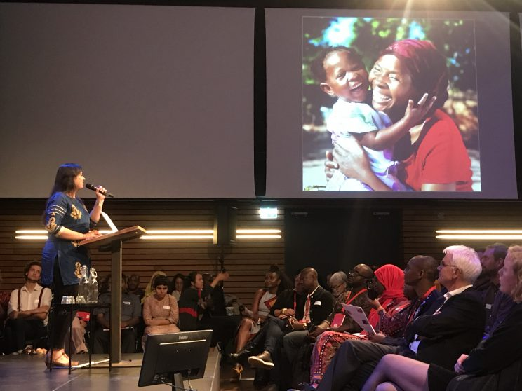 nidhi talking in the microphone on a stage in front of an audience. There is a screen necxt to her with the image of a small child and a woman