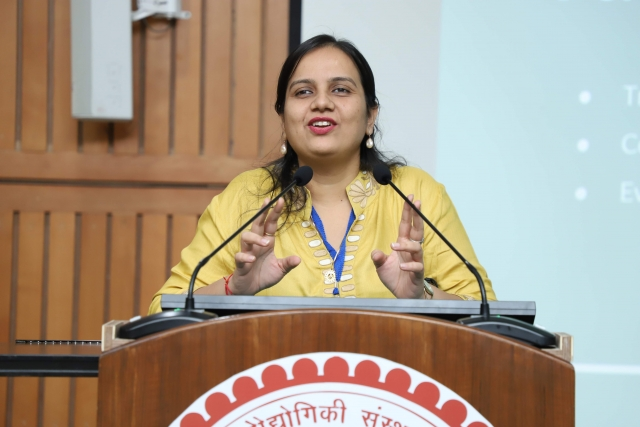 Nidhi goyal wearing a yellow kurta, speaking at a podium at empower 2019 at IIt delhi