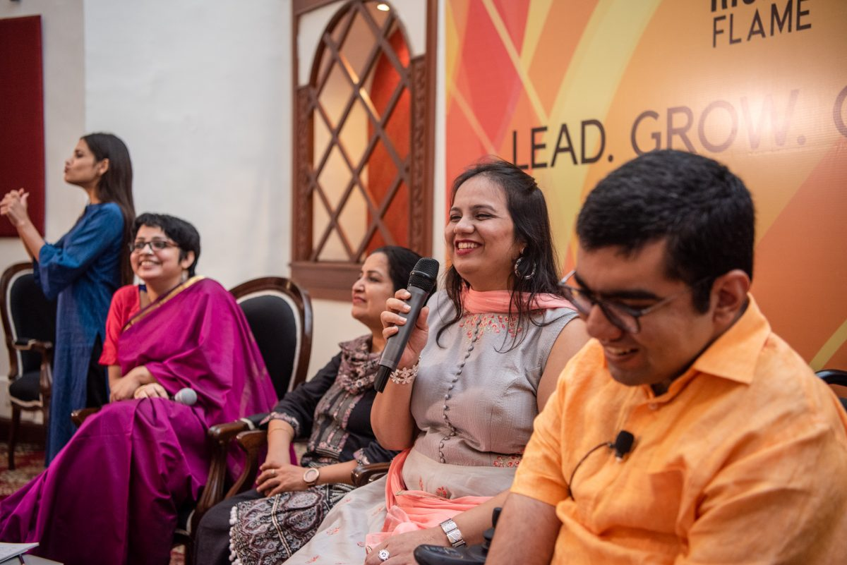 Nidhi goyal smiling and holding the mic. on her right sits srinidhi raghavan and harpriti reddy. on her left sits nipun malhotra. sign language interpreter stands on the left