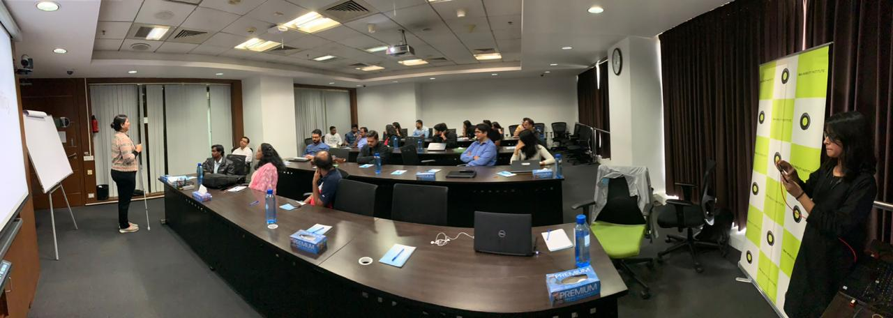 a panoramic image of the room. Nidhi standing in the front . a projector screen behind her. The audience sitting and listening
