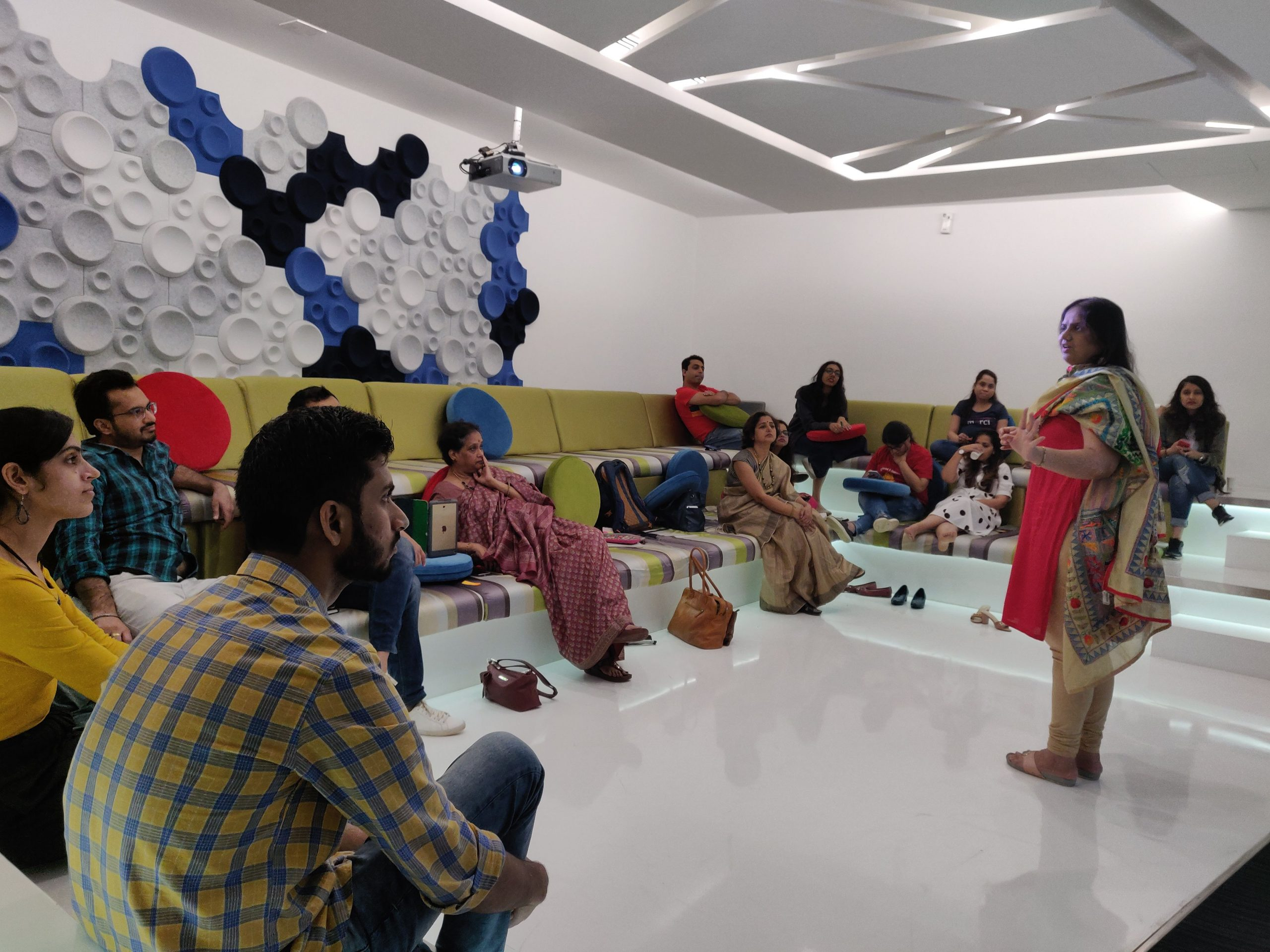 nidhi goyal standing in the front and speaking while participants sit around the room listening intently. the room has white walls a geometric blue and white design on the walls