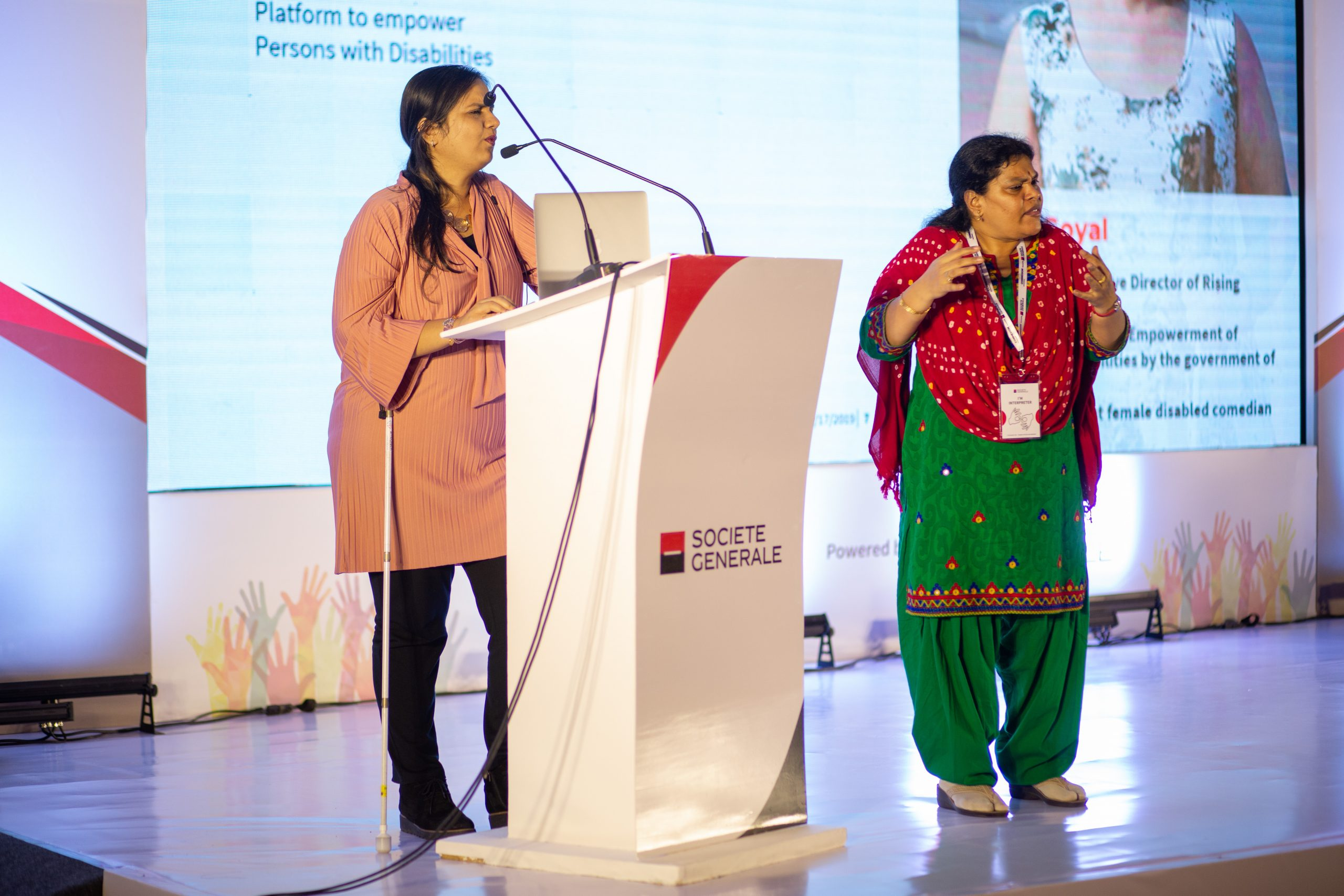 "On the left of the image, Nidhi standing and speaking at a white podium with the words ""Societe Generale"" written on it. On her right, the sign language interpreter stands and translates for the audience. A large white screen behind them, with a slightly blurred picture and bio of Nidhi on it."