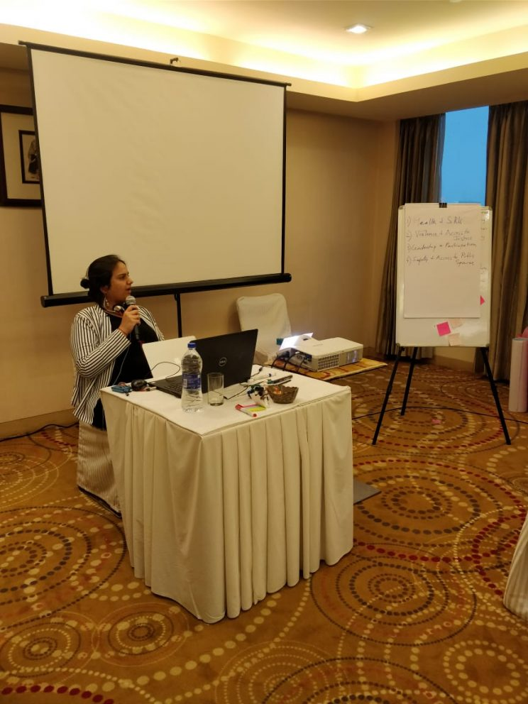 nidhi goyal sitting a white table in a room with a golden carpet. there's a projector screen behind her and a white board in the left corner