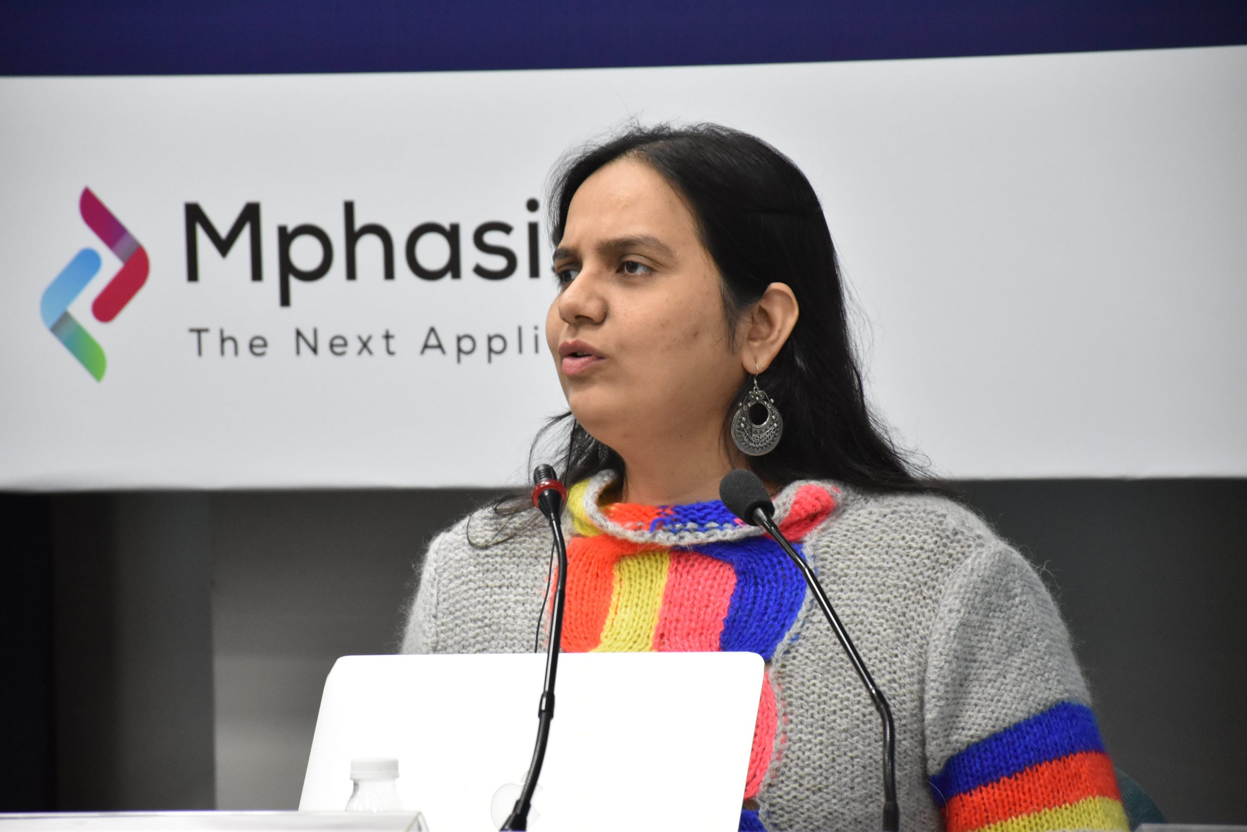 Nidhi goyal speaking. in front of her are two mics and a silver laptop. her hair is down and she is wearing a greu sweater with orange and blue stripes. behind her is a board that says mphasis