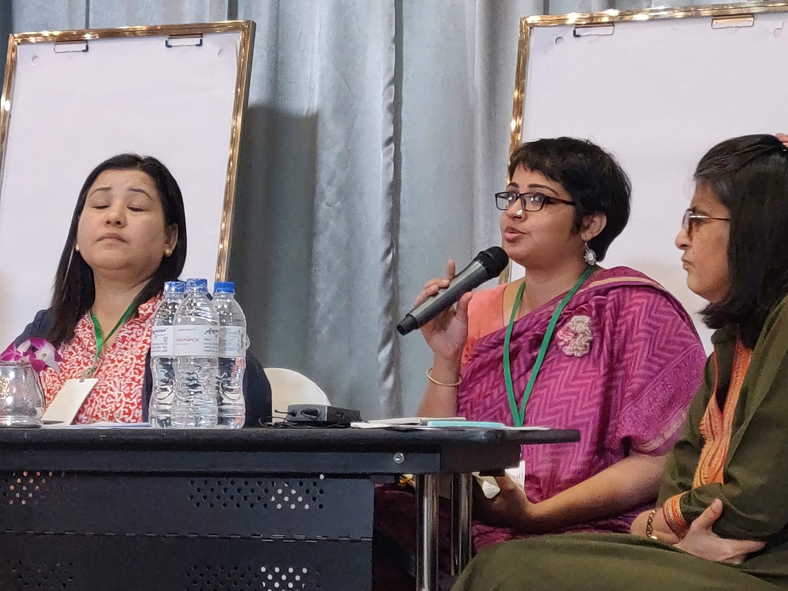 srinidhi raghavan holding a mic in front of her face. she is wearing a pink saree and and ID card with a blue band. beside her sit renu addlakha and pratima gurung. behind the three of them are two white boards