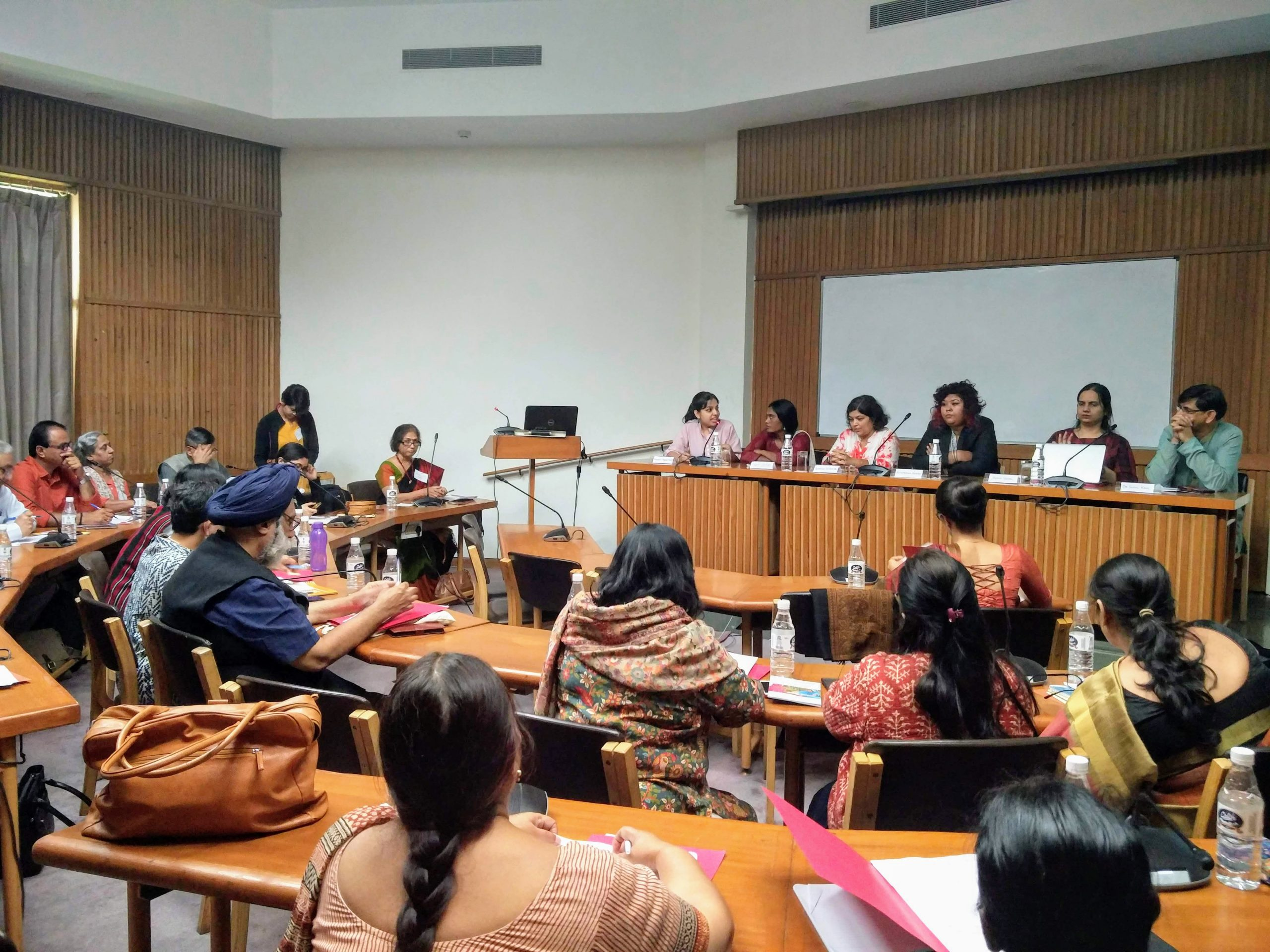 A room with brown bamboo walls. Tables arranged in multiple rows in a semi circle form. Approximately 15 people are sitting in these rows. Towards the front of the room, a long rectangualr table, at which 6 panelists sit. 2nd from the right is Nidhi Goyal. There is a laptop on the letf corner of the room on a podium.