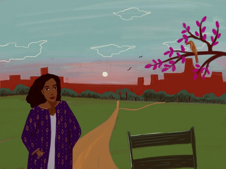 A woman dressed in a purple overcoat is walking through a park with a bench and trees nearby. Behind her we can see the outline of the city as a silhouette in red. She has her hands in her overcoat and there is road near her.