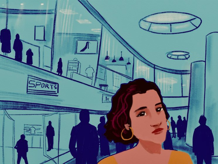 The image is the inside of a mall with windows of the stores and many people walking around the mall. In the middle is a close up of a woman's face with short hair and red highlights in the hair. She is wearing loops in her ears.