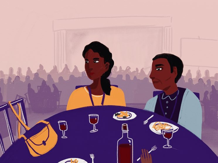 A woman and a man sitting at a table with a purple tablecloth in a large crowded room. Food and drinks are kept on the table, and a third person's hand is visible at the edge of the image. The man is looking at the woman, while the woman looks away pointedly. Behind them, you can see pink silhouettes of other tables and people sitting. A woman and a man sitting at a table with a purple tablecloth in a large crowded room. Food and drinks are kept on the table, and a third person's hand is visible at the edge of the image. The man is looking at the woman, while the woman looks away pointedly. Behind them, you can see pink silhouettes of other tables and people sitting.