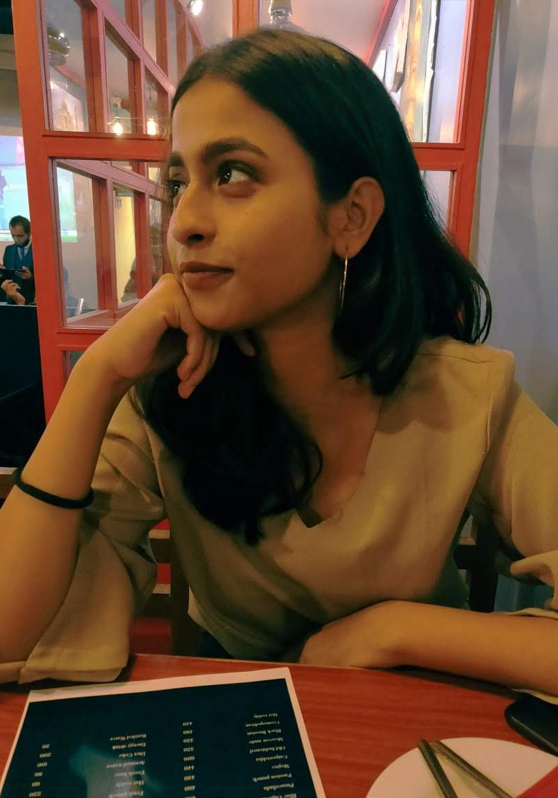 Chayanika is sitting in a cafe in front of a red window. She has a hand under her chin and is looking to her right, smiling. She is wearing silver, round earrings and a beige shirt.